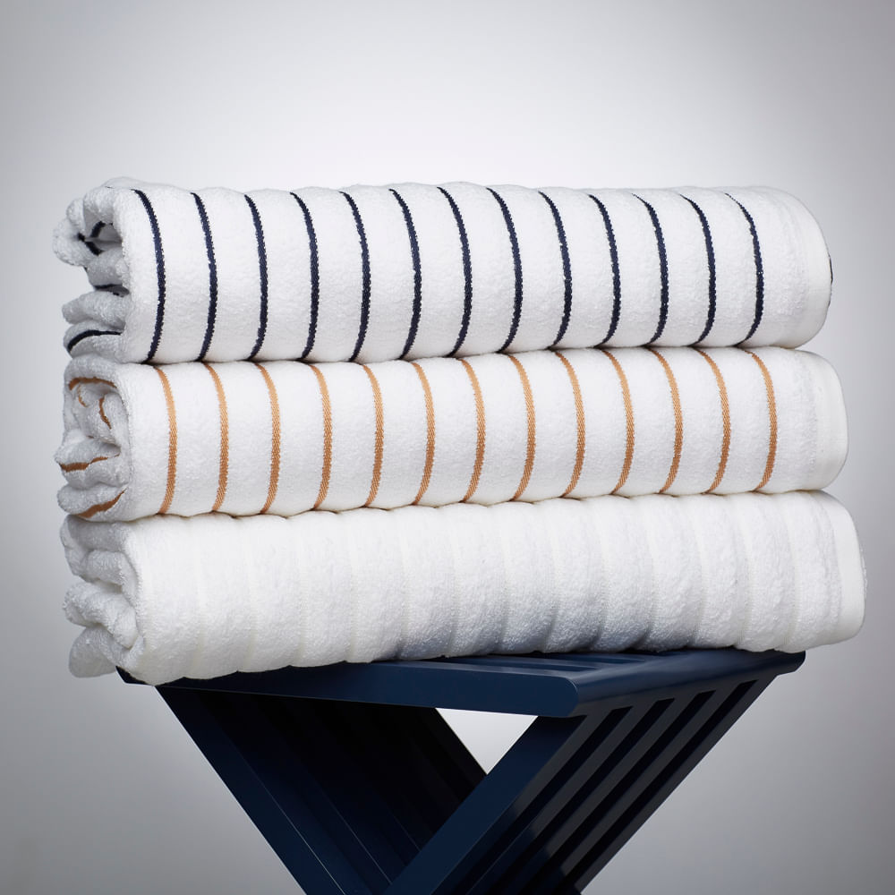 Stack of 100% cotton luxury beach towels in a variety of colors